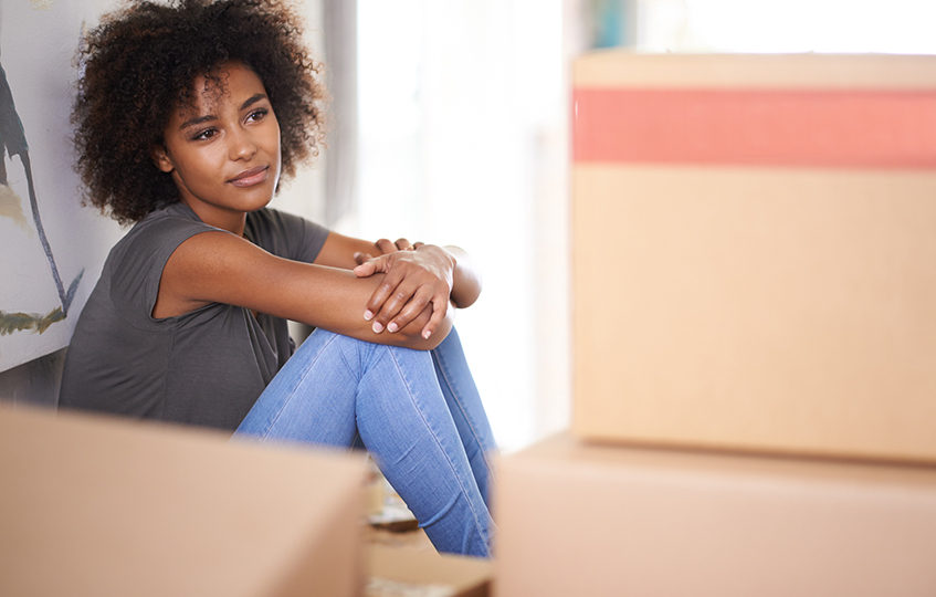 Shot of young woman feeling nostalgic while sitting amongst packed boxes