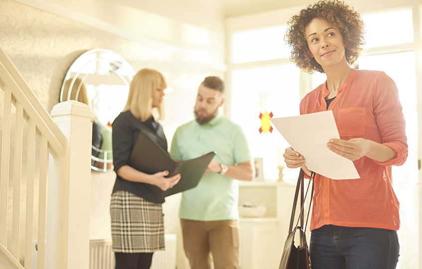 a young couple view a property guided by an estate agent. They are entering the hallway of house and the man is asking the estate agent about the property whilst the woman is picturing herself living in the property.