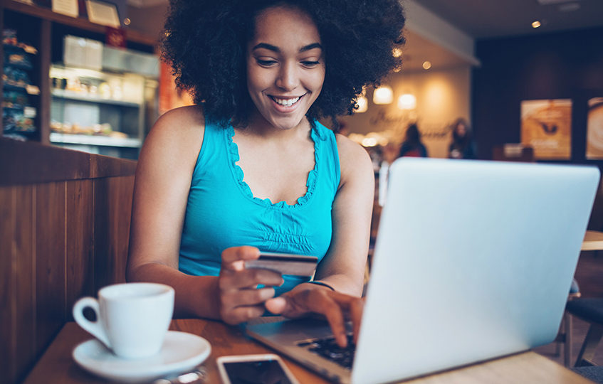 Smiling young woman sitting in cafe, holding a credit card and typing on a laptop.