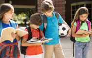 Elementary-age children, friends on school campus head back to school.