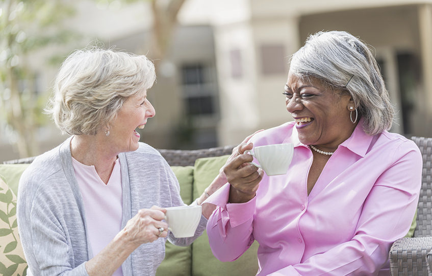Two retired women drinking tea and laughing in the garden
