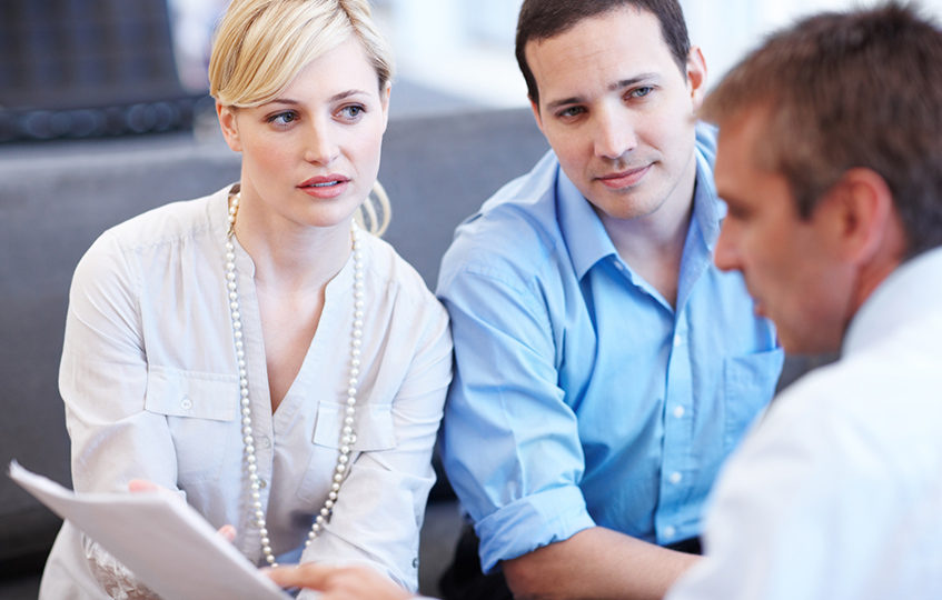 Young couple discussing a document with their advisor