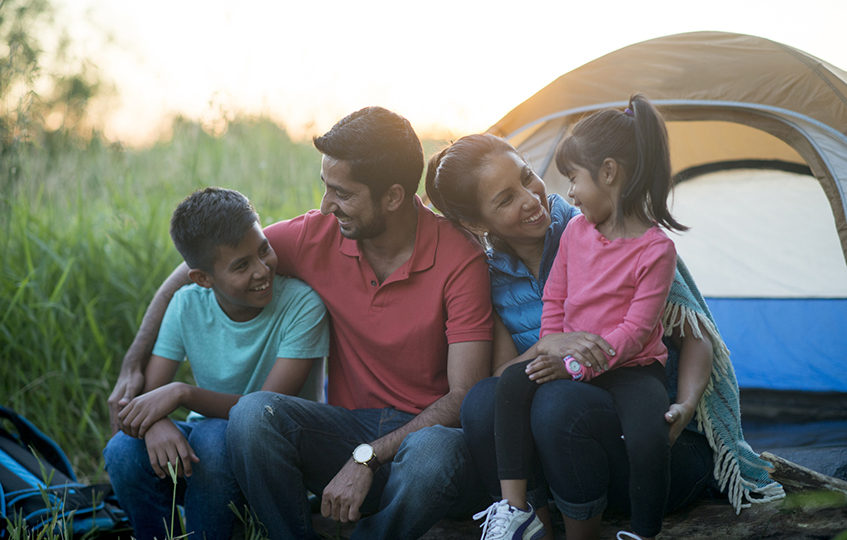 A family is on a summer vacation together. They are on a camping trip and are sitting in the grass next to their tent.