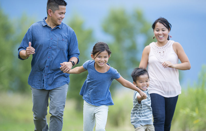 A family of four are walking happily through a grassy field on a spring evening. They are holding hands and enjoying nature.