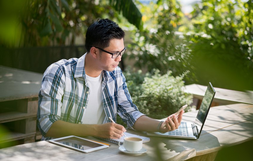 Asian man looking at his phone and working on his laptop outdoors