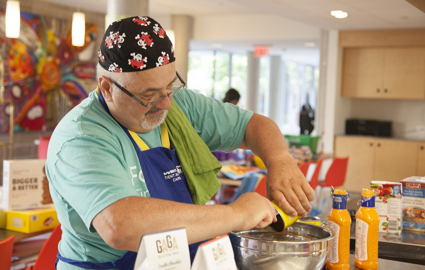 Retired man making food at a charity event